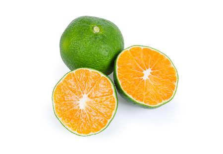 Toda la mandarina verde madura y la mandarina cortada por la mitad sobre un fondo blanco.