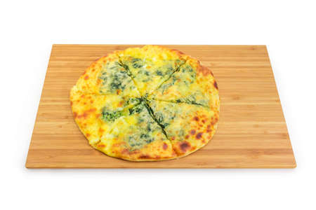 Round khachapuri with cheese and greens on the wooden bamboo cutting board on a white background Stock fotó