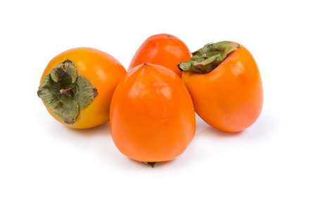 Several fresh ripe whole persimmon fruits on a white background