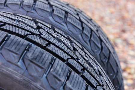 Fragment of the car tires with aggressive tread at selective focus on a blurred background of fallen leaves 版權商用圖片