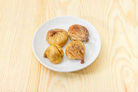 Dried fig fruits on the white saucer on light colored wooden surface 版權商用圖片