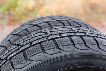 Fragment of the car tires with asymmetric tread on a blurred background