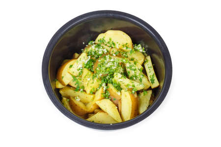 Top view of inner pot of household electric multi-cooker with potato slices baked in it and sprinkled with chopped parsley and garlic on a white background