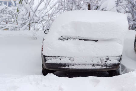Back part of the car covered with thick layer snow after a snowstorm