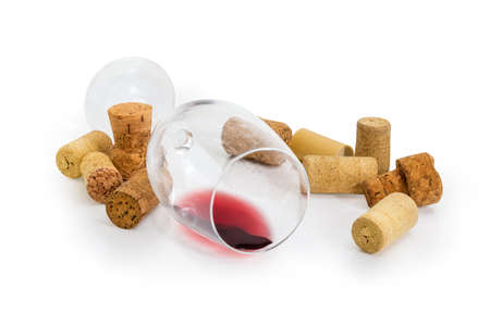 Wine glass lying on its side with small amount of red wine among of different wine cork on a white background Stock fotó