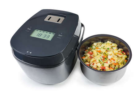 Household electric multi-cooker and inner pot pulled out with various vegetables braised in it on a white background Stock Photo
