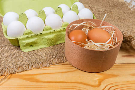 Brown chicken eggs in round wooden box on background of white eggs in open carton made of recycled paper pulp on a rustic table with sackcloth at selective focus Stock fotó