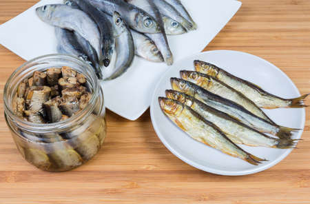 Smoked baltic herring on saucer and headless baltic herring preserved in vegetable oil in glass jar against of raw fish on a bamboo wooden surface Foto de archivo