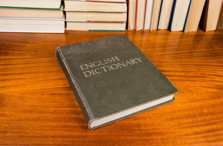 Closed old hardback english dictionary with cloth cover on a wooden table on a background of other books