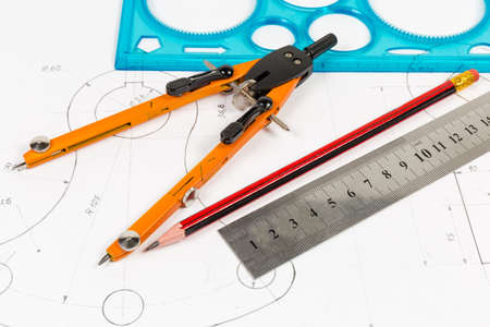 Top view of the pencil, different rulers and drawing jointed pair of compasses on a training drawing close-up