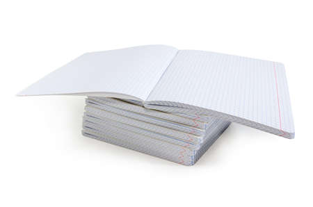 Open blank exercise book with pages of squared paper and red vertical lines for a margins on a stack of other same  exercise books on a white background