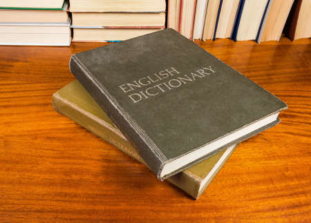 Two volumes of the large old hardback english dictionary with cloth cover on a wooden table on a background of other books Stok Fotoğraf