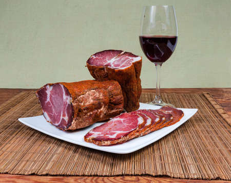 Partly sliced dried pork neck on the square white dish and glass of red wine on bamboo table mat on rustic table 版權商用圖片