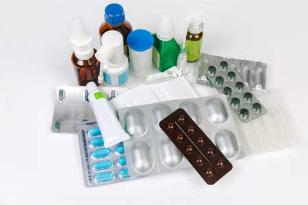 Various pills, ointment, sprays, powdery and liquid medicines in different types of packaging on a white table