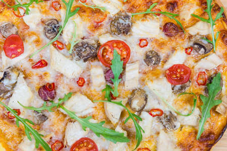 Background of cooked pizza with chicken meat, frankfurters, button mushrooms, tomatoes and arugula. Fragment close-up