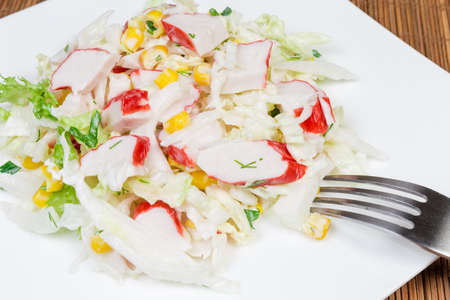 Salad of сrab sticks with napa cabbage, sweet corn and greens on square white dish with fork close-up Reklamní fotografie