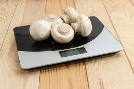 Several fresh cultivated whole white button mushrooms on the household digital kitchen scale on a light colored rustic wooden table