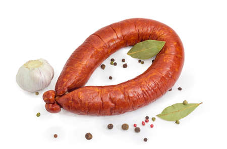 Pork bologna sausage in natural casing curtailed by a ring among scattered various spices on a white background Stock Photo - 116290131