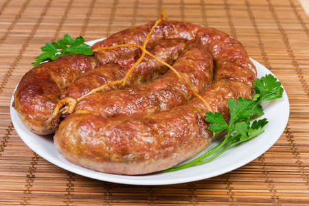 Fresh baked homemade turkey meat sausage curtailed by a rings, tied with twine and  decorated with parsley on dish on a bamboo table mat close-up at selective focus Stock Photo