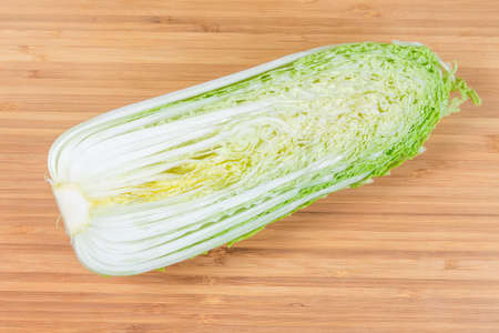 Half of head napa cabbage also known as chinese cabbage,  cut along on the bamboo wooden cutting board