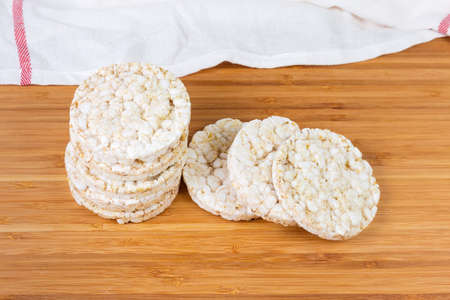 Dry round puffed crispbreads made from brown rice on a bamboo wooden surface