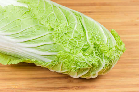 Upper part of head napa cabbage also known as chinese cabbage on the bamboo wooden cutting close-up 스톡 콘텐츠