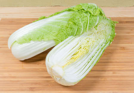 Two halves of head napa cabbage  cut along, also known as chinese cabbage on the bamboo wooden cutting board 스톡 콘텐츠