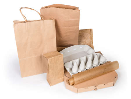 Different brown paper food packaging bags, carton box,  egg box and other recyclable packing for various foods on a white background