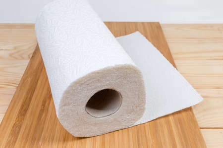 Roll of two-ply paper towels with tear-off sheets on wooden surface close-up