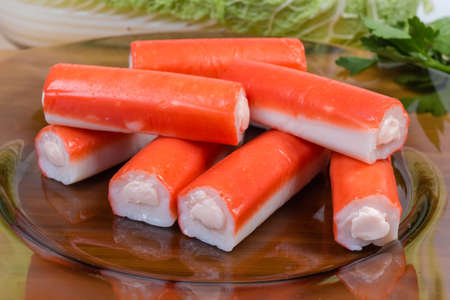 Crab sticks stuffed with processed cheese spread on the dark glass dish close-up at selective focus