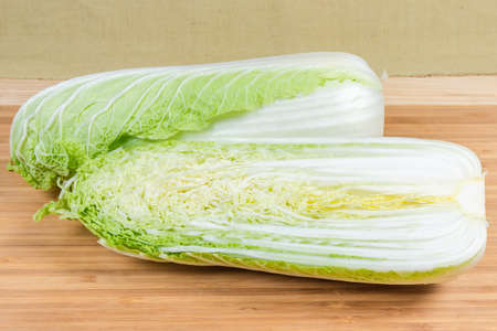 Whole and half cut along of heads napa cabbage also known as chinese cabbage on the bamboo wooden cutting board