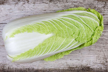 Top view of whole head of napa cabbage also known as chinese cabbage on an old cracked wooden surface
