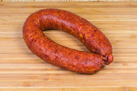 Boiled-smoked pork sausage known as bologna sausage in natural casing curtailed by a ring on the wooden bamboo cutting board Stock Photo