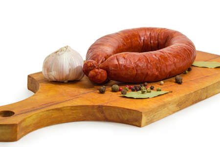 Pork bologna sausage in natural casing curtailed by a ring among scattered various spices on the wooden cutting board on a white background