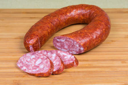 Partly sliced boiled-smoked pork sausage known as bologna sausage in natural casing curtailed by a ring on the wooden bamboo cutting board Stock Photo
