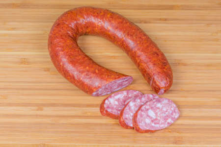 Top view of the partly sliced boiled-smoked pork sausage known as bologna sausage in natural casing curtailed by a ring on the wooden bamboo cutting board Stock Photo - 117840522