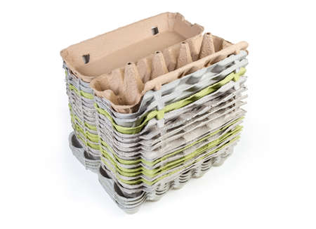 Stack of different open empty egg cartons made of recyclable paper pulp on a white background