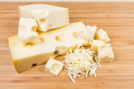 Partly sliced and grated Swiss-type cheese with large holes known as cheese's eyes on a bamboo wooden cutting board