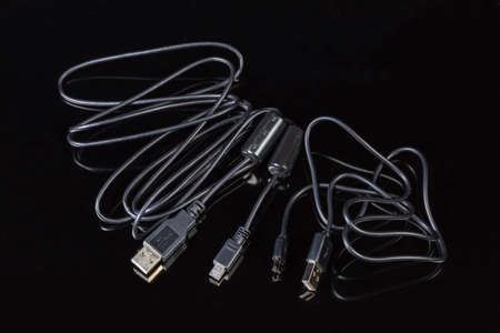Two black cables with plugs USB standard A and mini-USB standard B, USB standard A and micro-USB standard B at the edges on a dark reflective surface