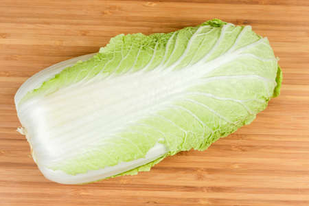 Top view of whole head of napa cabbage also known as chinese cabbage on a bamboo wooden cutting board close-up