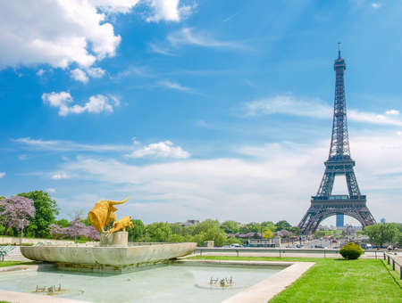 View of the Eiffel Tower from the Trocadero Square with fountain and sculptures in the foreground on the background the sky with clouds in Paris. Stok Fotoğraf