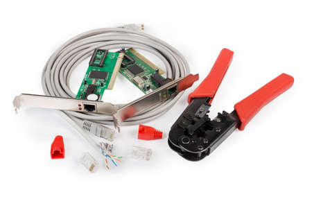 Crimping tool for twisted pair, connectors and red protective caps, cables, two different network controller cards on a white background