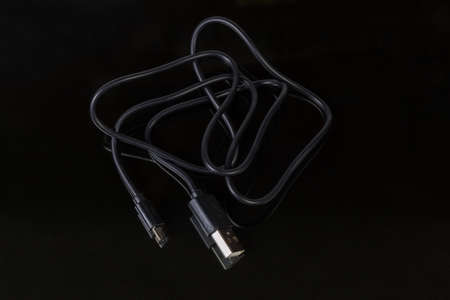 Black cable with plugs USB standard A and micro-USB standard B at the edges at selective focus on a dark reflective surface