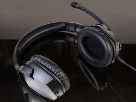 Black wired high-fidelity headset with full size headphones close-up on a dark reflected surface Banque d'images