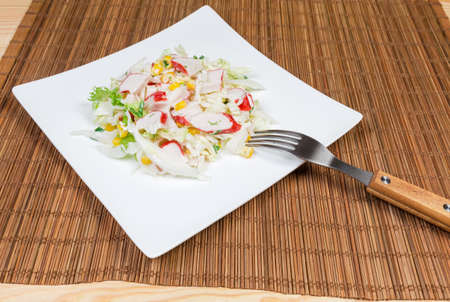 Salad of сrab sticks with napa cabbage, sweet corn and greens on square white dish with fork on a bamboo table mat