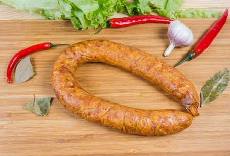 Boiled-smoked pork bologna sausage in natural casing curtailed by a ring among some spices and vegetables on the wooden cutting board