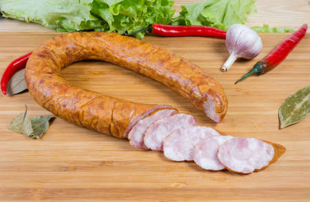Partly sliced boiled-smoked pork bologna sausage curtailed by a ring among some spices and vegetables on the wooden cutting board Stock Photo