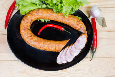 Top view of the black dish with partly sliced boiled-smoked pork bologna sausage curtailed by a ring among some spices and vegetables on the wooden rustic table