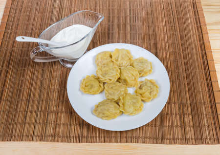 Cooked homemade meat dumplings, also known as pelmeni on white dish and sour cream sauce in glass gravy boat on the bamboo table mat Stock Photo