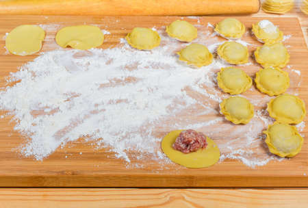 Raw homemade meat dumplings, also known in Eastern European cuisine as pelmeni during their preparation on the wooden cutting board Stock Photo